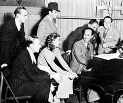 L to R: seated: Fred Astaire, Ginger Rogers, George Gershwin; standing: dance director Hermes Pan, film director Mark Sandrich, lyricist Ira Gershwin, and music director Nathaniel Shilkret (1936)